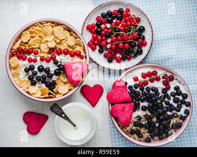 Festive and healthy breakfast for loved ones. Cereal biscuits in pink glaze, vintage bowls, cornflakes, granola, yogurt, fresh berries. Close-up, top  - Stock Photo