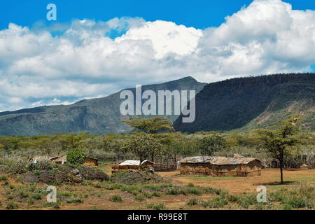 Traditional Masai homesteads at the foothills of Mount Suswa, Rift Valley, Kenya - Stock Photo
