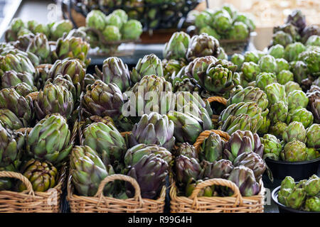 Buckets of Globe Artichokes for sale on a Canadian market in Montreal, Quebec. Artichokes are massively producted in America, and consumed on most of  - Stock Photo