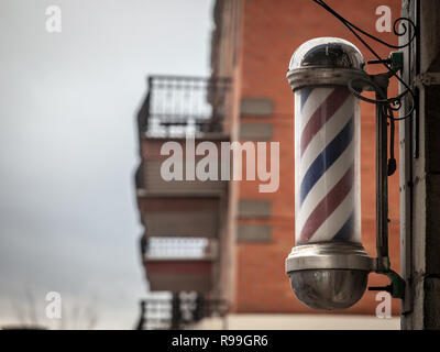 Typical American barbers pole seen in front of a barber shop of Montreal, Canada. This pole is a vintage sign indicating the presence of a male hairdr - Stock Photo