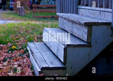 Dead leaves by old wooden stairs in fall setting. - Stock Photo