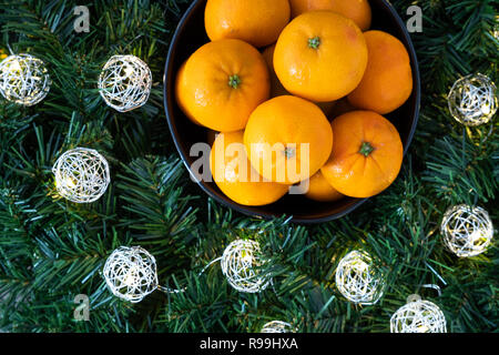Bunch of satsuma oranges in a black bowl, in a wreath with LED Christmas lights on a wood background - Stock Photo