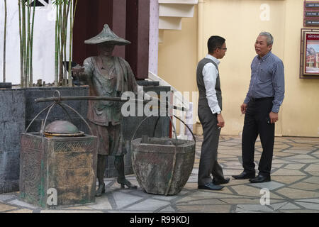 White-collar workers in Far East Square, Singapore, having a cigarette break next to a sculpture depicting a Chinese food vendor of old - Stock Photo