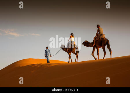 Morocco, Errachidia Province, Erg Chebbi, tourists on camels ride through dunes at sunset - Stock Photo