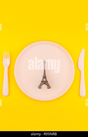 Small Eiffel tower love symbol plate serving plastic tableware copy space on bold yellow background in creative minimal style. Concept Valentine love  - Stock Photo