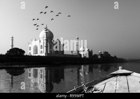 Taj Mahal reflected in Yamuna River view from wooden boat in black and white. - Stock Photo