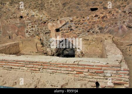 The remains of a communal bath within the ruins of the ancient Roman city of Pompeii, Italy, that was destroyed by Mount Vesuvius erupting in 79AD - Stock Photo