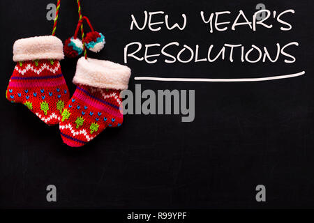 The word New Year's resolution written on the blackboard with a mittens. - Stock Photo