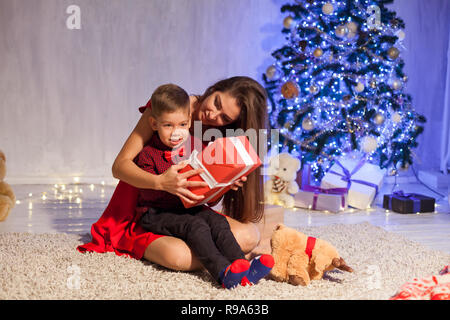 mother and son open Gifts Christmas New Year holiday Garland lights - Stock Photo