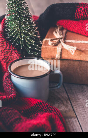 Hot coffee mug wrapped in a cozy woolen scarf for winter days with christmas tree and decoration elements - Stock Photo