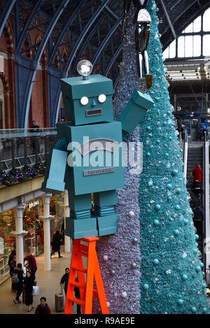 St Pancras Station, London, UK. 21st December 2108. A giant robot on a stepladder at the Tiffany & Co tree in St Pancras ststion. Credit: Matthew Chattle/Alamy Live News - Stock Photo