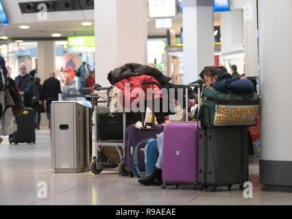 Berlin, Germany. 21st Dec, 2018. Travellers sit on a bench at Tegel Airport and wait for their flight to be called. Credit: Paul Zinken/dpa/Alamy Live News - Stock Photo