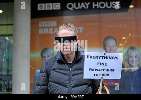 Salford, UK. 21st Dec, 2018. An Extinction Rebellion campaigner wearing a blind fold over his eyes and holding a placard which reads 'Everythings fine I'm watching the BBC', BBC, Media City, Salford, UK, 21st December 2018 (C)Barbara Cook/Alamy Live News Credit: Barbara Cook/Alamy Live News - Stock Photo