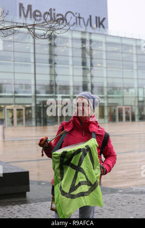 Salford, UK. 21st Dec, 2018. An Extinction Rebellion campaigner holding a ER symbol banner. BBC, Media City, Salford, UK. 21st Dec, 2018. (C)Barbara Cook/Alamy Live News Credit: Barbara Cook/Alamy Live News - Stock Photo