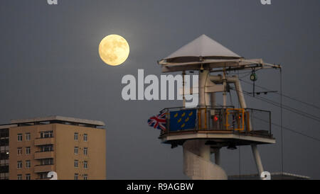 Brighton, Sussex, UK. 21st Dec 2018. A beautiful full moon rises above the zip wire ride on Brighton seafront this evening as the shortest day of the year comes to an end on the winter solstice Credit: Simon Dack/Alamy Live News  - Stock Photo