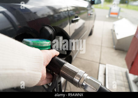 Female hand fill gasoline in a car with gas pump nozzle - Stock Photo