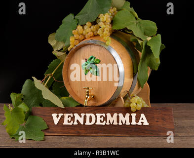 Table with vintage writing, with barrel of wine and grapes - Stock Photo