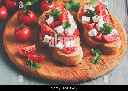 Bruschetta with tomatoes, cheese and cilantro on a cutting wooden board, rustic table. Selective focus, toned image - Stock Photo