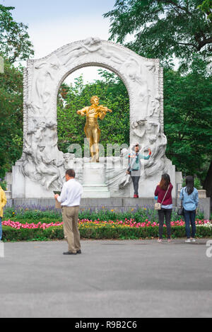 Vienna tourism, tourists visit the famous gold statue of Johann Strauss in the Stadtpark in Vienna, Austria. - Stock Photo