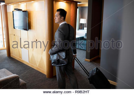 Businessman with suitcase arriving in hotel room suite - Stock Photo