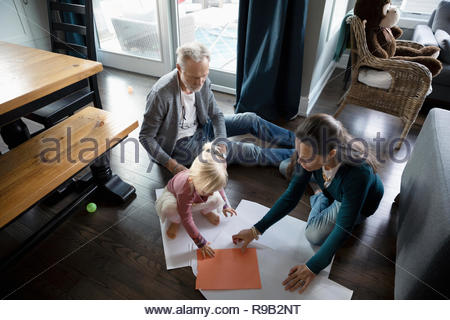 Grandparents and toddler granddaughter coloring on floor - Stock Photo