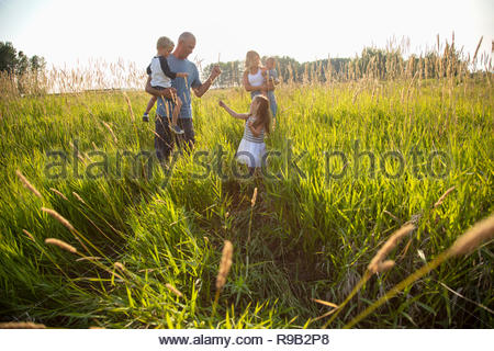 Young family in sunny, rural field - Stock Photo