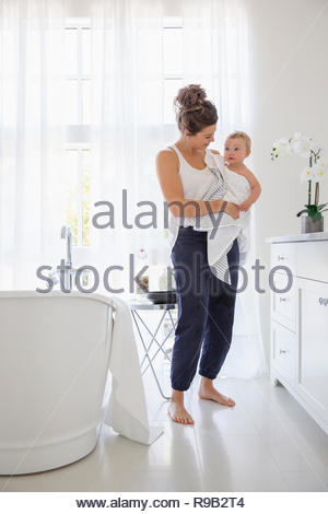 Mother holding baby daughter in towel after bath in bathroom - Stock Photo