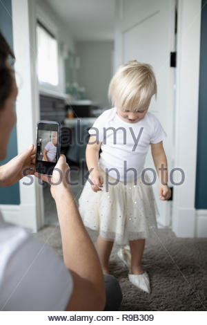 Father with camera phone photographing cute toddler daughter in high heels - Stock Photo