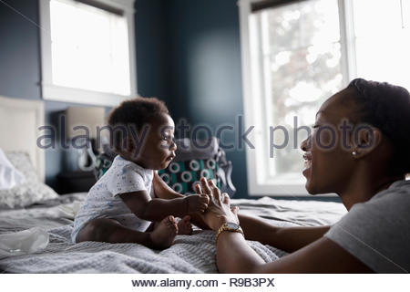 Mother and cute baby son on bed - Stock Photo