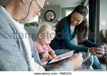Grandparents watching granddaughter coloring on digital tablet - Stock Photo