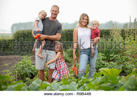 Portrait happy young family harvesting fresh vegetables in rural vegetable garden - Stock Photo
