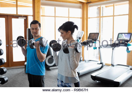 Personal trainer and client doing dumbbell biceps curls in gym - Stock Photo