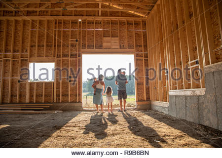 Family standing in sunny, rural barn under construction - Stock Photo