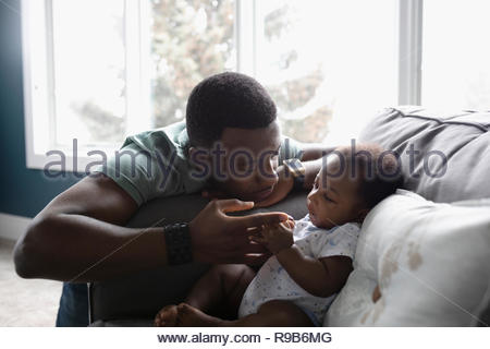 Affectionate father and baby son on living room sofa - Stock Photo