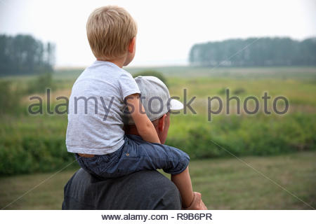 Father carrying son on shoulders on rural farm - Stock Photo