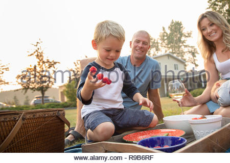 Playful boy with raspberries on fingers enjoying picnic with parents - Stock Photo
