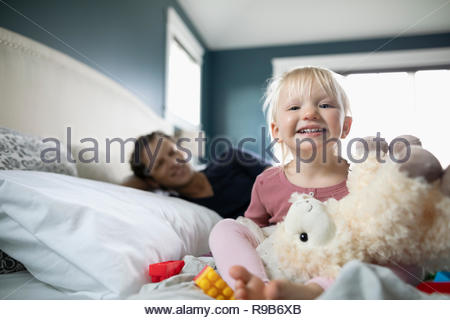 Portrait happy toddler girl playing with stuffed animal on bed - Stock Photo