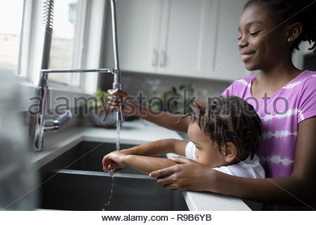 Sister helping toddler brother washing hands at kitchen sink - Stock Photo