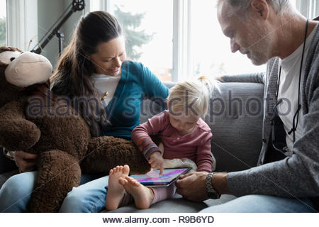 Grandparents watching granddaughter drawing on digital tablet - Stock Photo