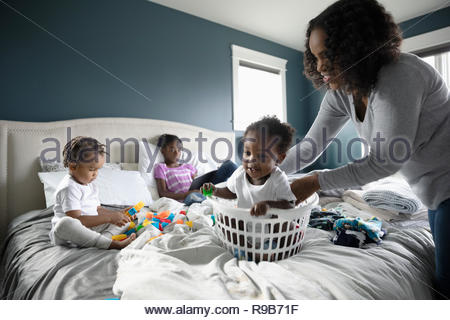 Playful mother placing baby son in laundry basket on bed - Stock Photo
