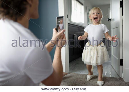 Father with camera phone photographing cute, playful toddler daughter in high heels - Stock Photo