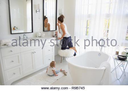 Baby daughter watching mother applying makeup in bathroom mirror - Stock Photo