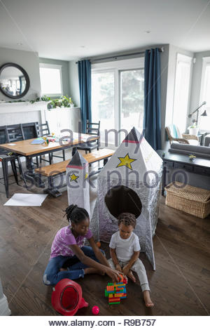 Brother and sister playing with toys on living room floor - Stock Photo