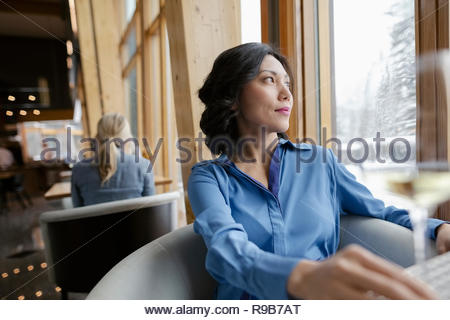 Confident, thoughtful businesswoman looking out restaurant window - Stock Photo