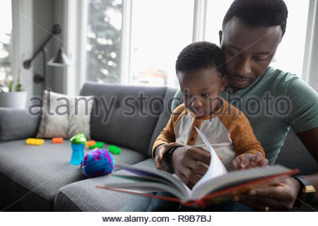 Father and toddler son reading book on living room sofa - Stock Photo
