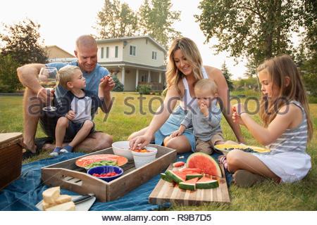 Young family enjoying picnic in rural yard - Stock Photo