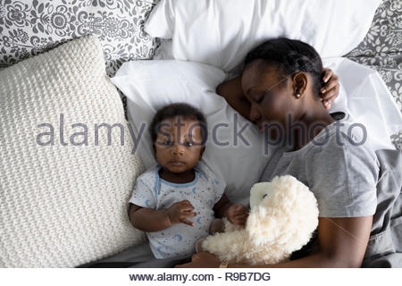 View from above mother and baby son napping on bed - Stock Photo