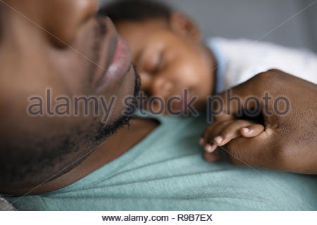 Close up affectionate father and baby son sleeping, holding hands - Stock Photo