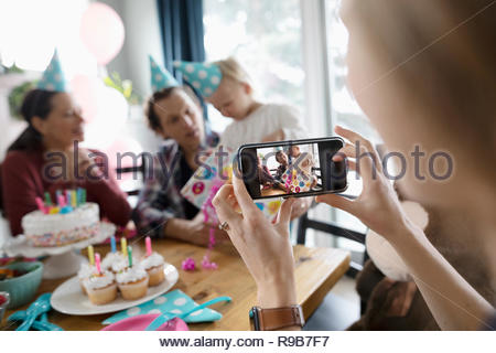 Woman with camera phone photographing toddler daughter opening birthday gift - Stock Photo
