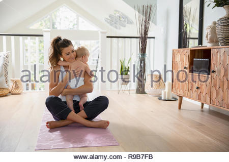 Affectionate mother holding baby daughter on yoga mat - Stock Photo